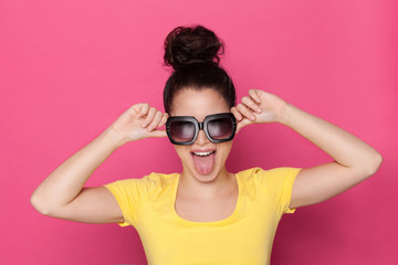 Young Woman In Big Sunglasses Is Stickin Out Tongue