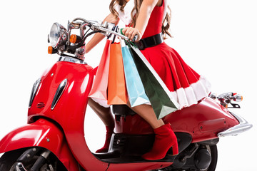 cropped view of girl in santa claus costume driving red scooter with shopping bags, isolated on white