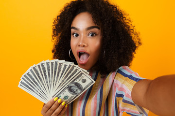 Excited young african woman posing isolated over yellow background holding money make selfie by camera.
