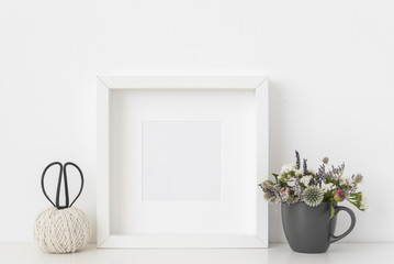 White square portrait frame mockup with dried field wild flowers in vase on white wall background. Empty frame, poster mock up for presentation design. Template frame for text, lettering, modern art.