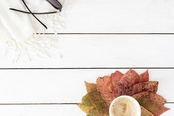 Autumn composition. Coffee and frame made of autumn colorful leaves, sunglasses on white background. Flat lay, top view, seasonal concept.