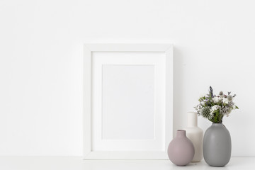 White A5 portrait frame mockup with composition of small vases and dried flowers on white wall background. Empty frame, poster mock up for presentation design.