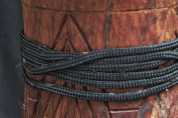 up-close view of a wooden African djembe design with tuning ropes