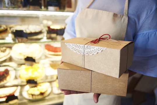 Close-up of woman holding cake boxes in a confectionery shop