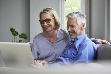 Happy mature couple sitting on couch at home sharing laptop