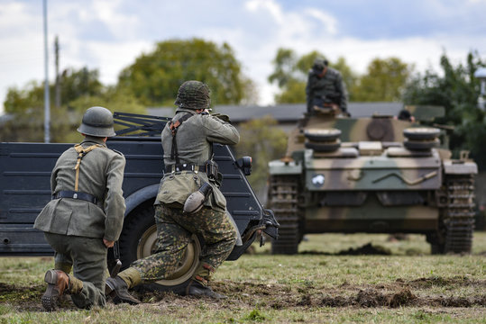 Historical reenactment of soldiers attacking a tank during the Second World War.