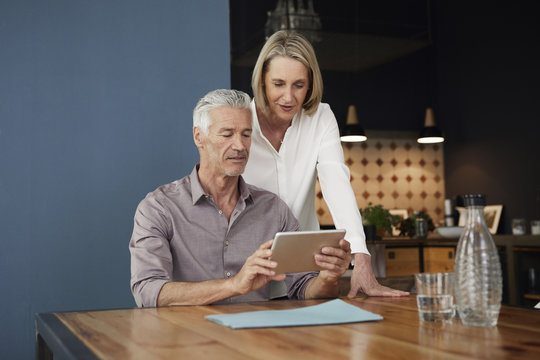 Mature couple using tablet at home