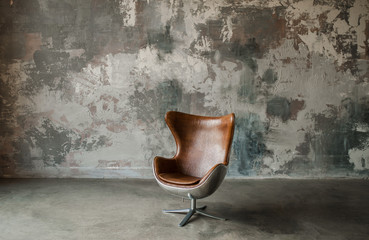 Loft interior mock up photo. Gray textured wall with leather armchair. Background photo with copy...