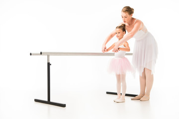 female teacher in tutu helping little ballerina practicing at ballet barre stand isolated on white background