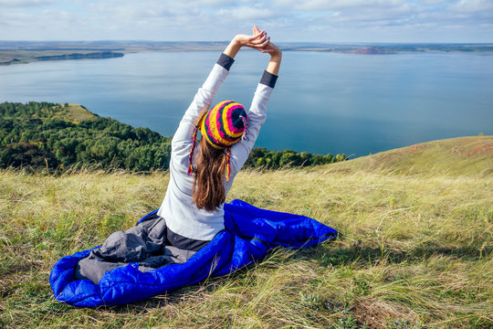 Young woman in a funny hat from Nepal in warm blue sleeping bag making the morning warm-up stretching against the background of a beautiful lake landscape