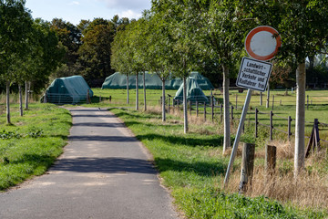 """walk in the park with a traffic sign at the side of the street with the german lettering """"Landwirtschaftlicher Verkehr frei"""" meaning agricultural traffic free"""