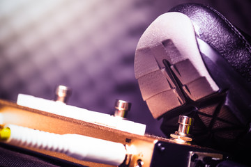 close up guitarist shoes pressing on guitar effect pedal buttons while playing electric guitar in sound studio