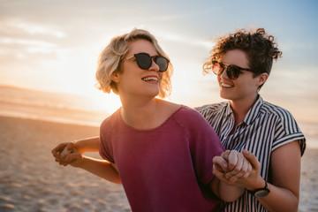 Fototapeta Laughing lesbian couple dancing playfully on a beach at sunset obraz