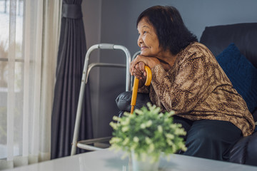 happy senior woman with wooden cane in living room