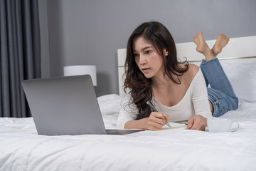 woman writing notebook and using laptop computer on bed