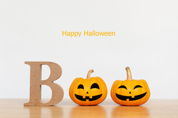 Pumpkin with alphabet BOO on wood table with white background. Halloween and decoration concept