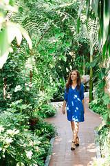 Young beautiful woman in blue dress walking in the botanical garden