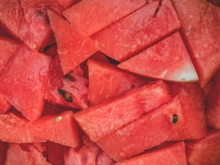 Slices of red fresh watermelon in a large plate in the green grass. Picnic in nature
