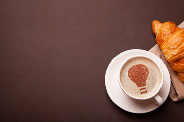 Cup of coffee with the idea symbol of light bulb on the foam. Coffee gives new ideas and creativity