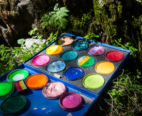 Compact vintage painter's case on grass with palette, artistic tools and abstract painting
