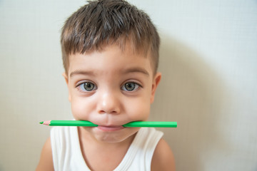 Cute baby boy toddler - with colored pencils in the mouth