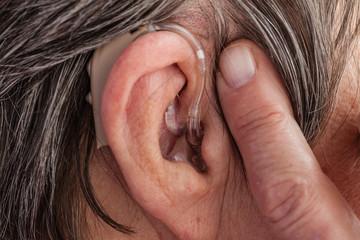 Closeup senior woman using hearing aid