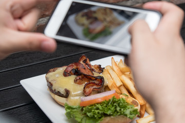 Man takes photo of food with mobile phone at an outdoor bar.  Taking a picture of your food with your phone. Hamburger, fries, and beer on a white plate outside on a black table, POV shot.