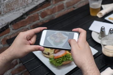 Point of view shot, man takes photo of food with mobile phone at an outdoor bar.  Taking a picture of your food with your phone. Hamburger, fries, and beer on a white plate outside on a black table.