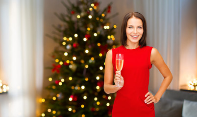 holidays and people concept - smiling woman in red dress with glass of non-alcoholic champagne over christmas tree lights background