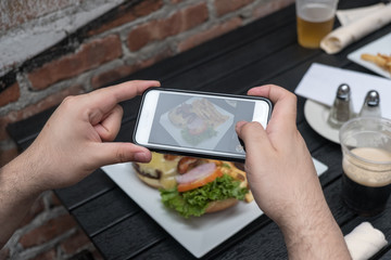 Point of view shot, man takes photo of food with cell phone at an outdoor bar.  Taking a picture of your food with your phone. Hamburger and fries on a white plate outside on a black table.