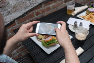 Point of view shot, man takes photo of food with mobile phone at an outdoor bar.  Taking a picture of your food with your phone. Hamburger and fries on a white plate outside on a black table.
