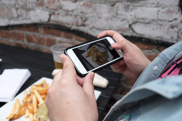 Man holding a mobile phone taking a photo of his food. Cell phone food photography. Taking a picture of hamburger, beer, and french fries at an outdoor pub with a smartphone.