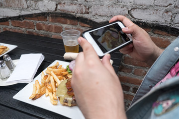 Man holding a mobile phone taking a photo of his food. Smartphone food photography. Taking a picture of hamburger, beer, and french fries at an outdoor bar with a cell phone.