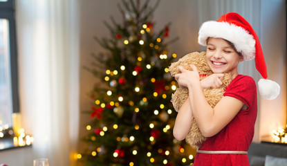childhood and holidays concept - smiling girl in santa hat with teddy bear over room with christmas tree background