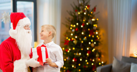 holidays, childhood and people concept - smiling little boy and santa claus with gifts over christmas tree at home background