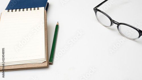 Wall mural Office desk table  notebook and pencil close up on white background