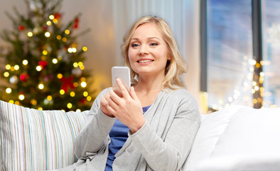 people, technology and holidays concept - smiling woman with smartphone messaging at home over christmas tree lights background