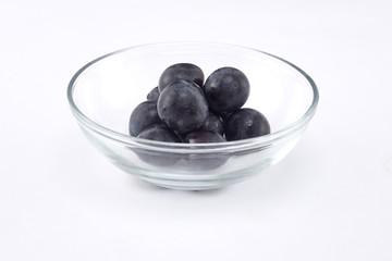 Fresh black grapes on white