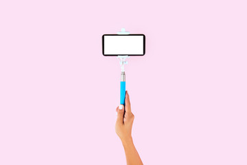 Selfie stick and white smart phone on pink background
