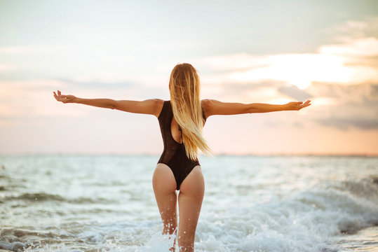 Outdoor lifestyle portrait of beautiful girl in black swimsuit