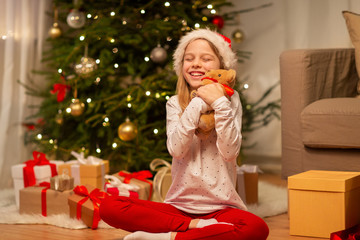 christmas, holidays and childhood concept - smiling girl in santa helper hat with gift box and teddy bear at home