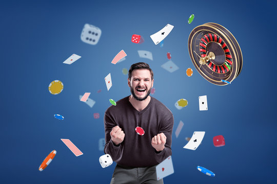 An emotional man cries angrily at camera, surrounded by a flying roulette, chips, cards and dice.