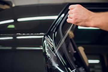 Worker hands installs car paint protection film wrap.