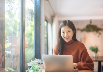 Happy young Asian girl working at a coffee shop with a laptop looking at camera.