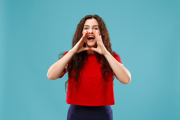 Do not miss. Young casual woman shouting. Shout. Crying emotional woman screaming on studio background. Female half-length portrait. Human emotions, facial expression concept. Trendy colors