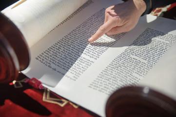 finger of boy reading scroll of jewish bible torah