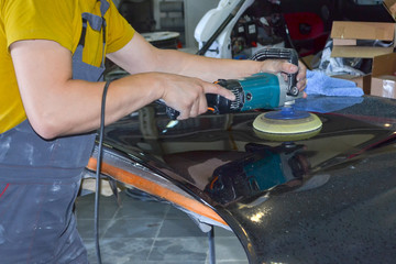 The master man of the detailing in work clothes and dirty hands polishes the bodywork of the bonnet of the car in black with a polishing machine in the workshop for body repair cars