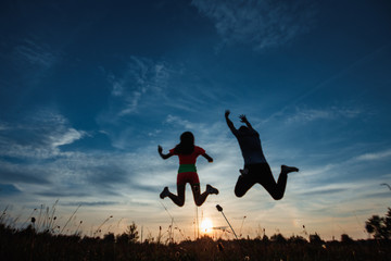 Happy young couple jumping against the beautiful sunset. Freedom, happiness, the concept of pleasure. A symbol of hope, freedom.