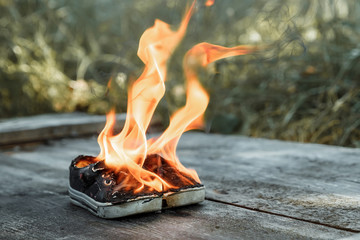 Creative background, burning shoes on a wooden background. The concept of sweat feet, bad smell, spoiled shoes after long use.