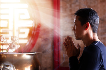 Faith and religious. .Man pressing hands together blessing in front of altar table at chinese shrine with sunlight through window,side view..